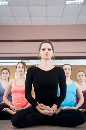 sukhasana: Five sporty yogi girls in class in Yoga pose sukhasana (Easy Pose, Decent Pose, Pleasant Pose)