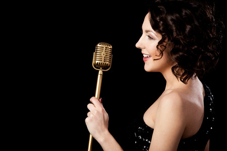 singer on stage: Elegant young female singer in shiny black evening outfit singing with smile, holding golden vintage microphone, live performance, concert, copy space