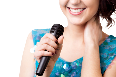 Smiling young female in sparkling blue dress, singing, holding microphone, close-up of mic, isolated on white background, copy space