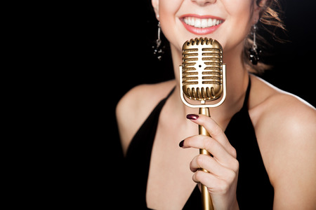 Elegant young female singer in black dress smiling holding golden vintage microphone, live performance, concert, unrecognizable person, close up, focus on mic, copy space