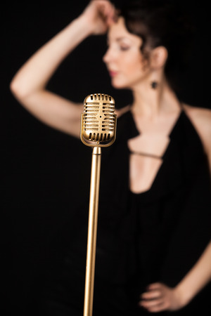 Beautiful emotional young female singer in sexy dress prepare to sing on the stage during live concert behind golden vintage microphone, focus on mic