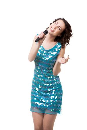 cantando: Joven delgada mujer con vestido azul brillante corto, divirti�ndose, cantando con dedicaci�n, con micr�fono, aislado en fondo blanco Foto de archivo