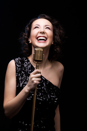 vocalist: Beautiful young female vocalist in shiny black evening dress happily laughing holding golden vintage microphone, on the stage during live musical show