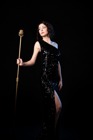 vocalist: Beautiful young female vocalist in shiny black evening dress prepare to sing during musical show, excitement, emotions before live concert, holding golden vintage microphone