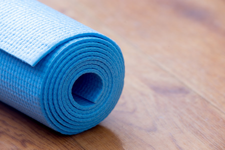 Close up of folded blue non-slip yoga, pilates mat on the floor. Healthy life, keep fit concepts, copy spase