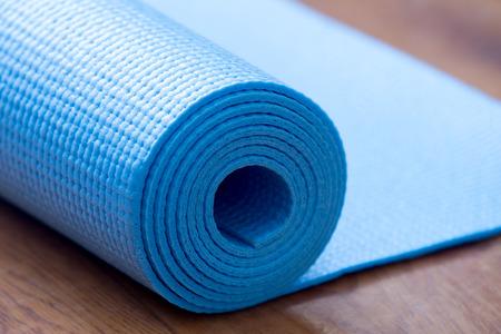 Close-up van opgerolde blauwe yoga, pilates mat op de grond. Gezond leven, fit blijven concepten