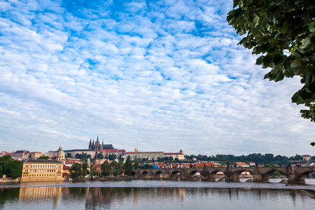 castle district: Tourism and sightseeing, view over remarkable sight of Prague Charles Bridge. Good weather, summer day, blue sky, calm river Vltava, the landmarks in Castle District in the distance