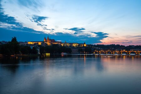 castle district: Tourism and sightseeing, view over remarkable sight of Prague Charles Bridge and Castle District. Good weather, summer night, calm river Vltava, the landmarks in the distance