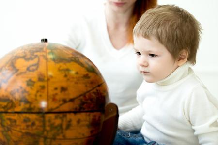 prodigio: Bambino Prodigy. Little boy guardando terre colorate globo. Mamma sullo sfondo. Focus sul bambino
