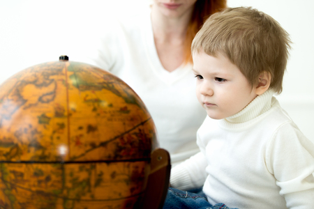 prodigy: Prodigy kid. Little boy looking at colorful earths globe. Mom on the background. Focus on child