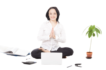 Business, study, healthy lifestyle, work at home. Serene young female worker surrounded by office accessories meditating in yoga Padmasana (Lotus Pose) palms touching in a gesture of namaste in front of laptop, isolated photo