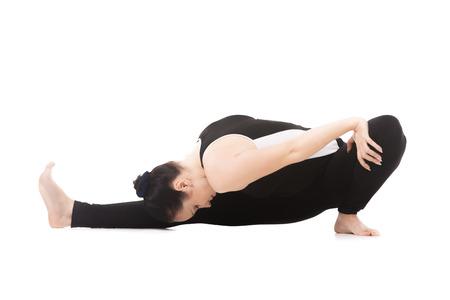 janu: Sporty yoga girl on white background doing fitness exercises, asana Janu Sirsasana Head-to-Knee Forward Bend Pose Stock Photo