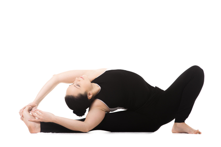 janu: Sporty yoga girl on white background doing fitness workout, asana Janu Sirshasana, Head to Knee Forward Bend Pose Stock Photo