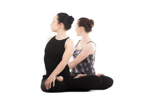 parivrtta: Sporty yogi female partners doing asana together, fitness training, yoga practice with partner, sitting, relaxing in pose parivrtta Padmasana, Lotus Position, isolated, white background