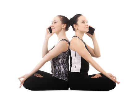 padmasana: Beautiful sporty yogi female partners doing fitness training together, yoga practice with partner, sit in pose Padmasana, Lotus Position, talking on the cell phone, holding smartphone