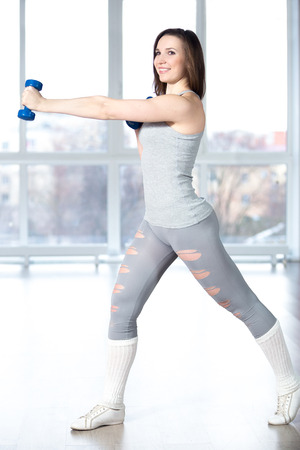 girl working out: Sporty smiling pretty girl working out in light sports hall with dumbbells, doing weight training