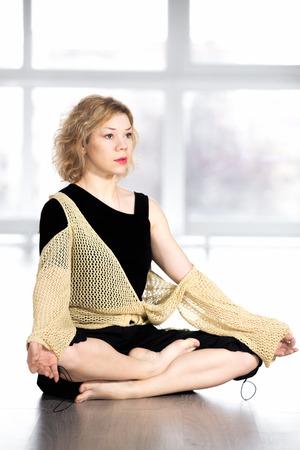 sukhasana: Sporty yogi woman resting, sitting cross-legged, relaxing in yoga pose sukhasana (Easy Pose, Decent Pose, Pleasant Pose)