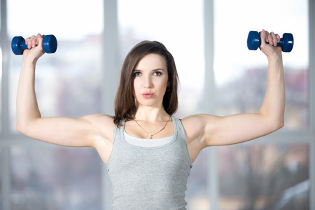 Sporty girl athlete leading active lifestyle, doing fitness training for biceps in grey sportswear with dumbbells, lifting weights, warming up, breathing, exhaling, exhausted Stock Photo