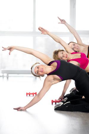 allenamento fitness, gruppo di tre donne sportive giovani e mid-età facendo piegamenti, esercizi per colonna vertebrale, la flessibilità, la perdita di peso, il riscaldamento durante la lezione di sport