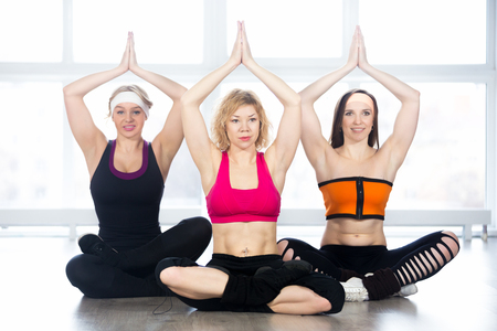 Sporty yogi girls doing fitness exercises in class, sitting in Yoga pose sukhasana (Easy Pose, Decent Pose, Pleasant Pose) with palms in Anjali Mudra above head