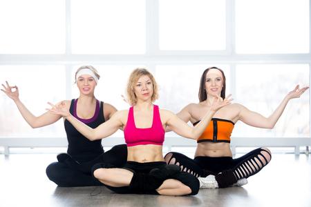 decent: Sporty yogi girls doing fitness exercises in class, sitting in Yoga pose sukhasana (Easy Pose, Decent Pose, Pleasant Pose), repeating posture after coach
