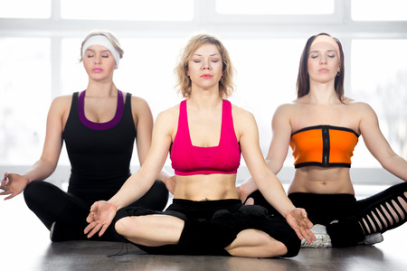 decent: Sporty yogi girls meditating in class, sitting cross-legged in Yoga asana sukhasana (Easy, Decent, Pleasant Pose), concentrating on breathing, resting, relaxing, repeating posture after coach