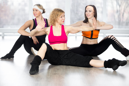 Sporty fitness instructor conducts aerobics training, group of three smiling women doing dynamic sport exercises with choreographic elements in class photo