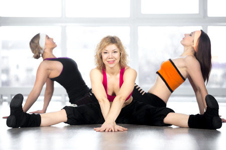 zumba: Attractive smiling mature mid age dancer female having choreography workout in group in fitness class, doing splits