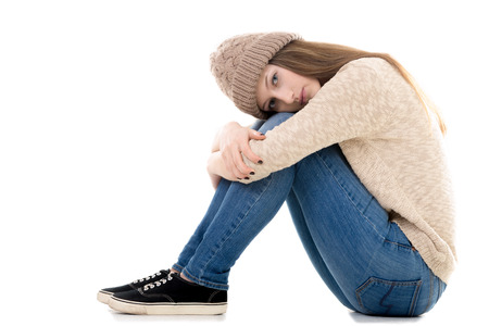 teenage girl: Sad teenage girl with problems sitting with her head on her knees, copy space Stock Photo