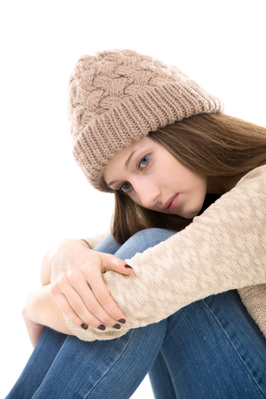 transitional: Teens troubles. Unhappy teenage girl sitting clasping her knees, looking down