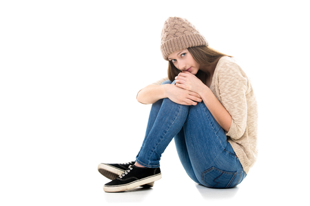 hugging knees: Teens troubles. Unhappy teenage girl curled-up, needs help, looking scared, copy space