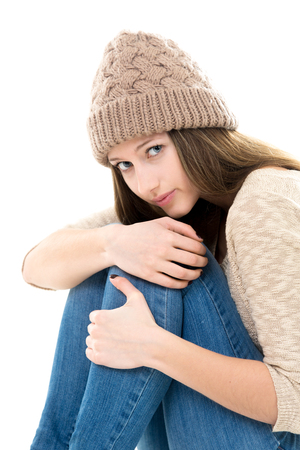 hugging knees: Teens troubles. Frightened teenage girl curled-up, looking afraid, upset, timid