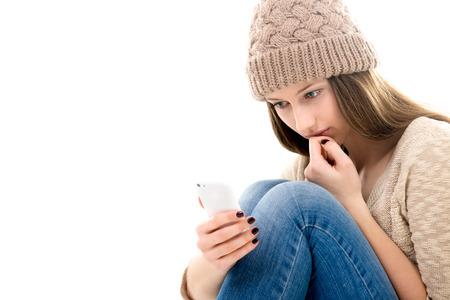 femme triste: Situation de vie difficile, des problèmes relationnels. Sad adolescente recroquevillée, en regardant son smartphone, lisant le message, en attendant l'appel, copie, espace