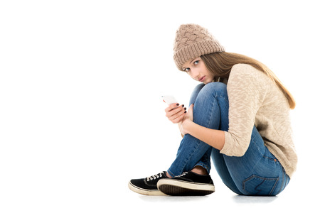 heartbreak issues: Difficult life situation, relationship problems, rebellious age. Teenage girl holding smartphone, waiting for call or message, looking anxious, copy space