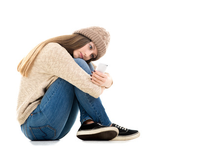 hugging knees: Relationship problems, teens problems. Teenage girl waiting for call or message, looking at smartphone, copy space Stock Photo