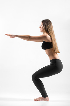 Young slim beautiful girl doing squat, fitness exercises for hips and buttocks photo