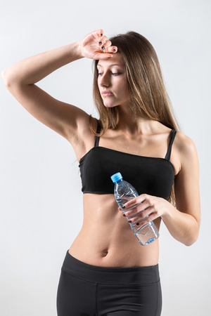 perspiration: Slim sporty girl holding a bottle of water resting after fitness training, tired