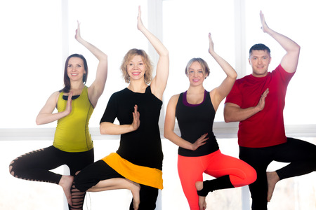vriksasana: Group of four positive people doing yoga exercises in class, standing in asana, Tree Pose, vrikshasana (Vriksasana)