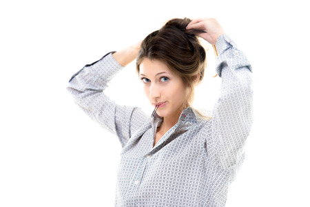 Beautiful young girl holding hairpin in her lips tying hair back, making hairdo with playful expression, copy space photo
