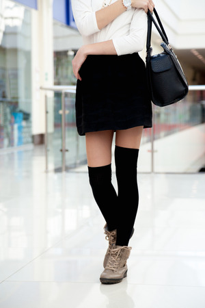 legwarmers: Female model in cute trendy outfit for shopping, office or study. Close-up on legs. Young shopper woman walking in short black skirt and wool stockings holding handbag
