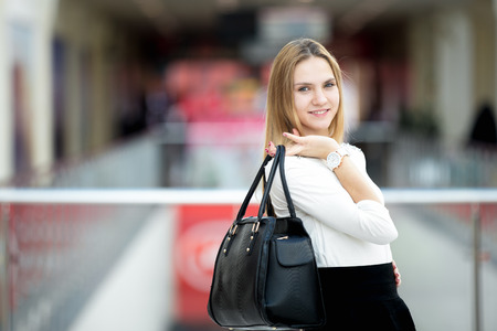 handbag: Slender young female model dressed in black and white stylish outfit holding leather handbag wearing matching wristwatch, posing, copyspace Stock Photo