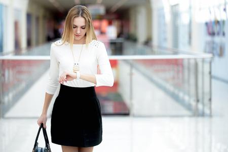 mujeres trabajando: Joven mujer de negocios en el moderno apresuramiento desgaste, esperando impaciente, mirando su reloj en una carrera, hacer recados, copia espacio