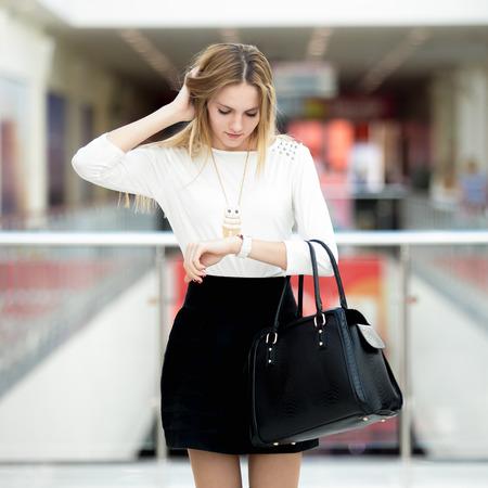 sgomento: Giovane donna di affari in vestito alla moda, tenendo la testa in sgomento, in ritardo per la riunione, fretta, in attesa, stressato, il controllo del tempo sul suo orologio in fretta