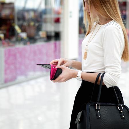 革製のハンドバッグの財布に探してかわいい流行の服の若いおしゃれな女性。財布と手にクローズ アップ