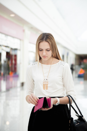 Upset young woman in shopping mall checking her purse with troubled look. Out of money, broke