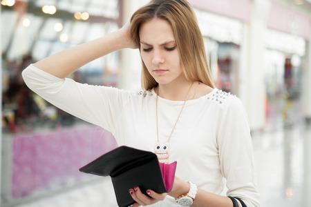 Retrato de mujer joven infeliz que mira en su cartera en el centro comercial, pasó demasiado, no lo suficientemente efectivo, pierde dinero, se rompió