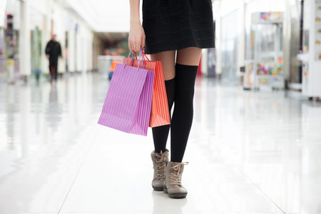 errands: Time for shopping. Young shopper woman walking in casual short black skirt and wool knee-high socks holding paper bags with purchases. Close-up of legs. Stock Photo