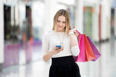 smartphones: Happy teenage girl holding bags with purchases, smiling while looking at phone in shopping center. Received good news, reading message, texting, dialing number, using app on smartphone Stock Photo