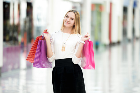 errands: Cheerful attractive young woman enjoying shopping, holding bright colored paper bags beside boutiques in outlet, copyspace Stock Photo
