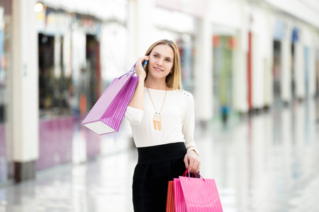 woman bag: Smiling happy young woman shopping, talking on mobile phone, holding vibrant colored paper bags, copyspace Stock Photo